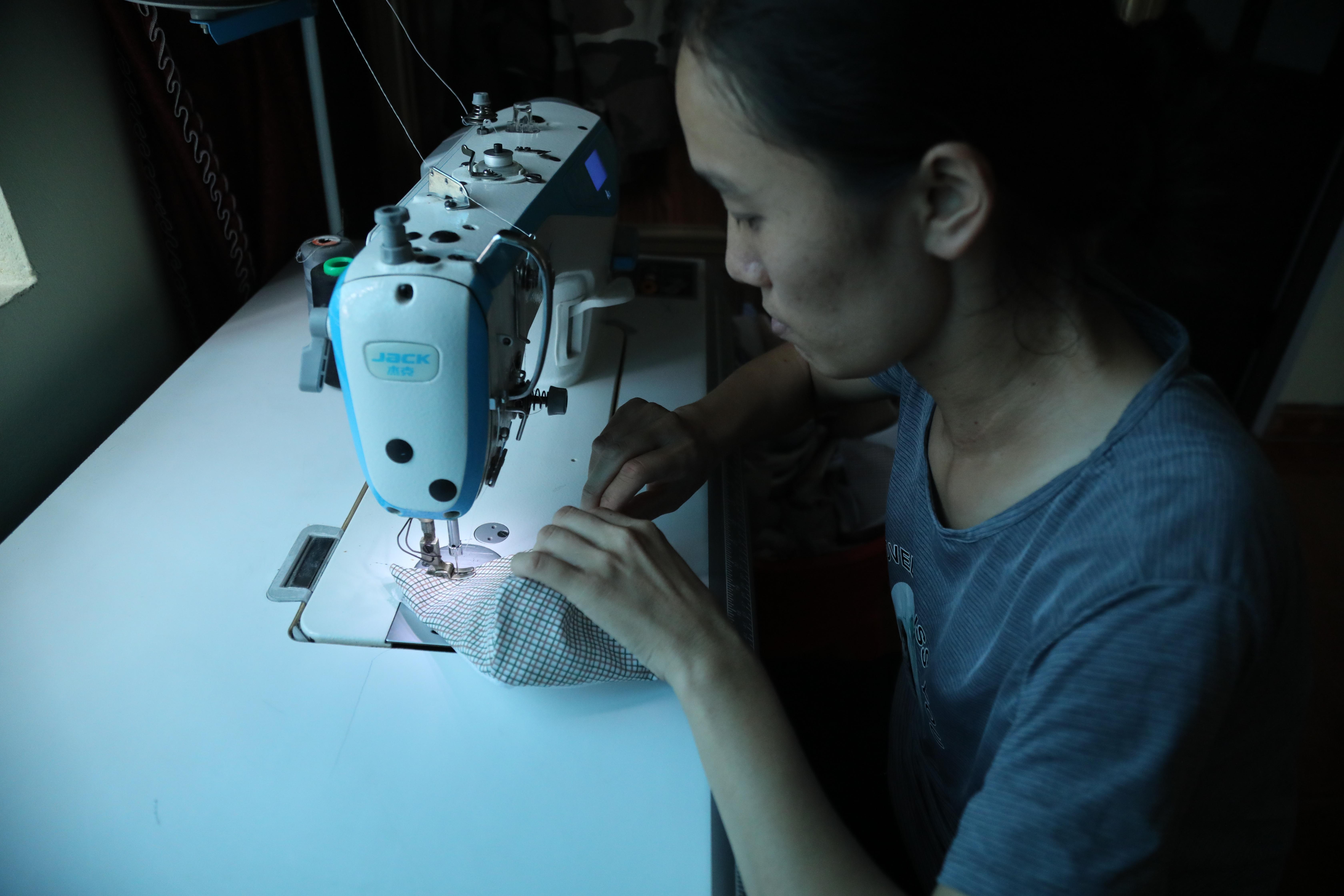 Chị Vũ Thị Tuyết bên chiếc máy khâu do Mặt trận trao tặng. Ảnh: Quang Vinh.