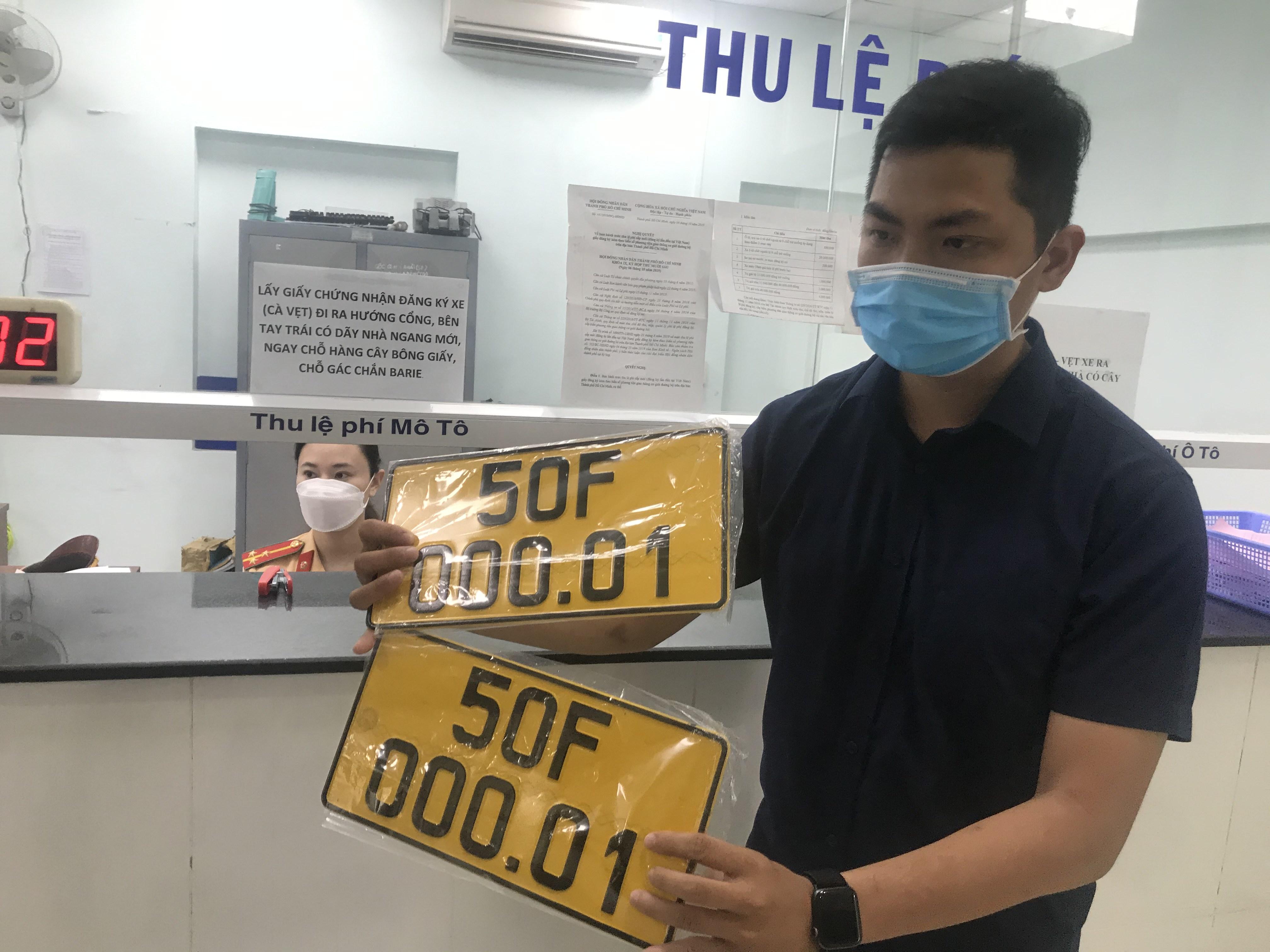 Một người dân vui mừng nhận biển số xe màu vàng.