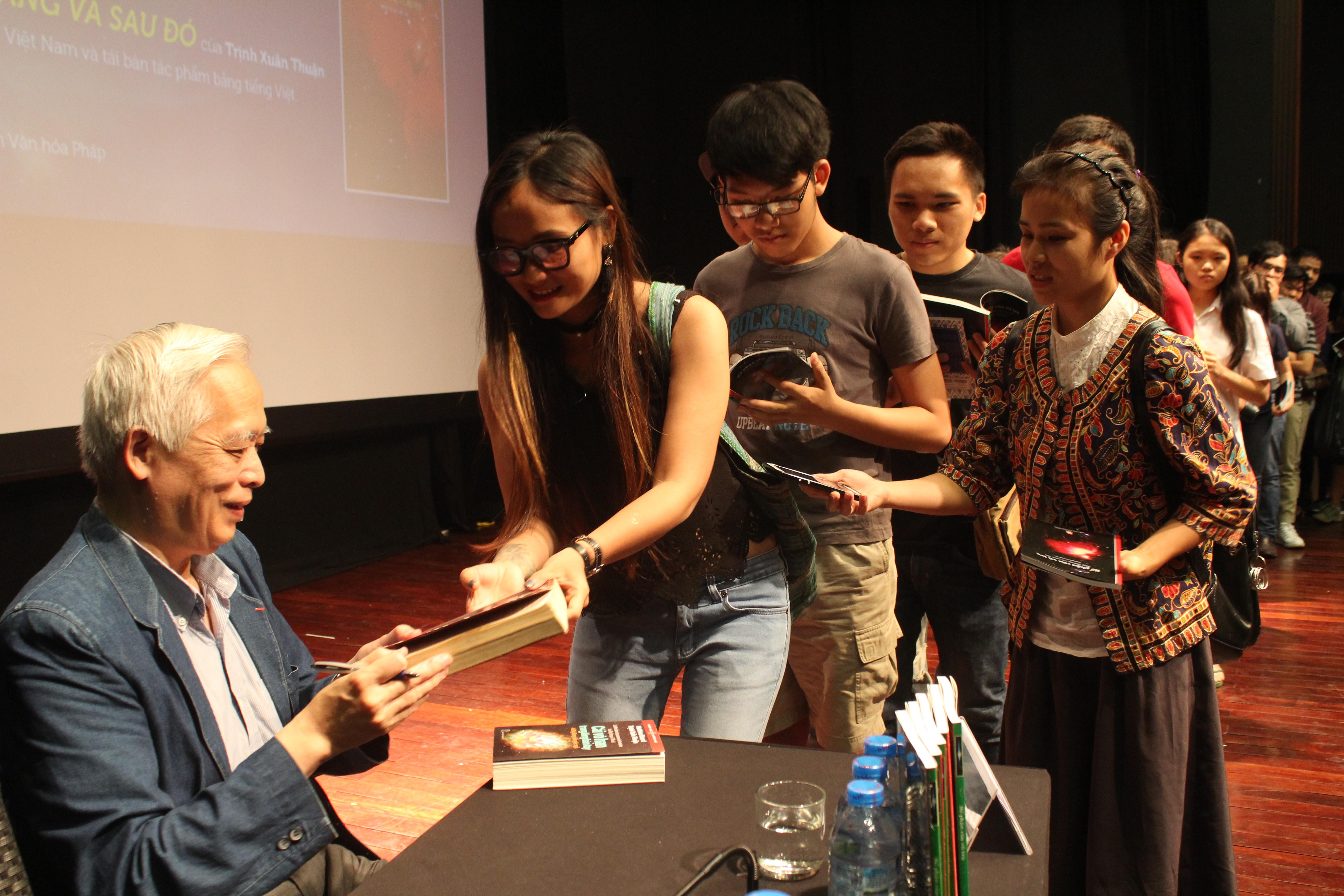 GS Trịnh Xuân Thuận tặng chữ ký cho độc giả trong lần về Việt Nam.