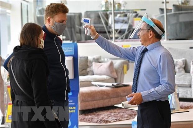 Khách hàng được kiểm tra thân nhiệt trước khi vào một cửa hàng ở London, Anh nhằm ngăn chặn sự lây lan của dịch Covid-19. (Ảnh: AFP/TTXVN).