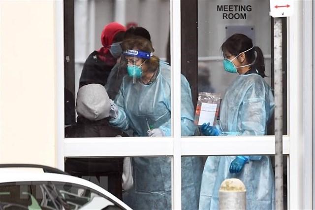 Nhân viên y tế lấy mẫu dịch xét nghiệm Covid-19 cho người dân tại Melbourne, Australia, ngày 6/7/2020. (Ảnh: AFP/TTXVN).