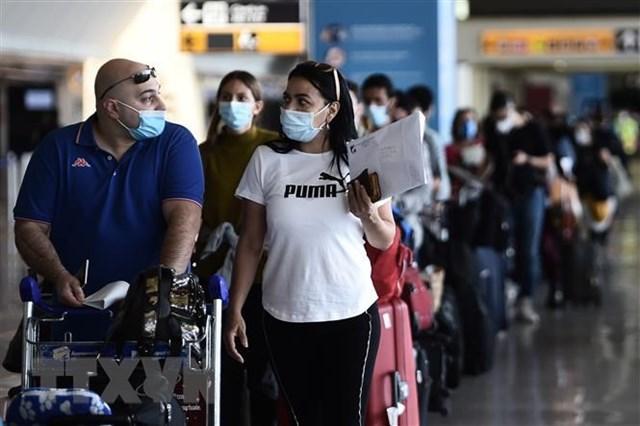 Hành khách đeo khẩu trang phòng lây nhiễm Covid-19 tại sân bay Fiumicino ở Rome, Italy. (Ảnh: AFP/TTXVN).