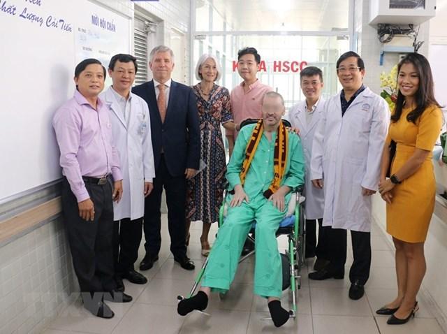 Bệnh nhân 91 chụp ảnh lưu niệm với đại diện Lãnh sự quán Anh tại Thành phố Hồ Chí Minh và các y bác sỹ trong ngày xuất viện. (Ảnh: TTXVN phát).