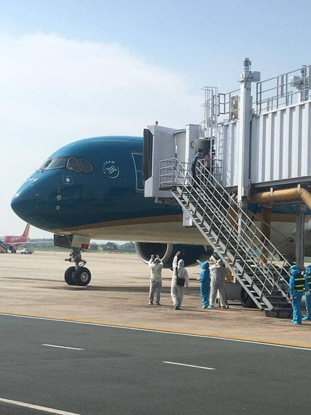 Bộ phận mặt đất mặc bảo hộ y tế tiếp nhận chuyến bay đến Nội Bài.