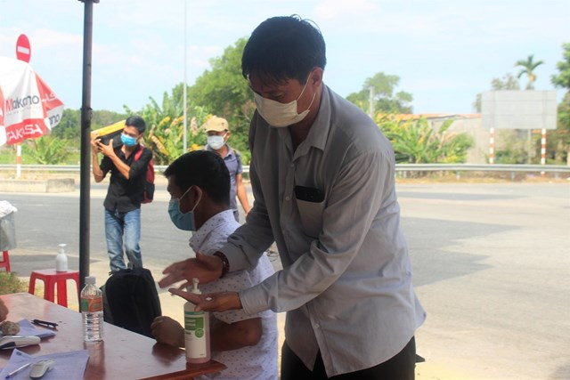 Người dân rửa tay sát khuẩn trước khi vào khai báo y tế.
