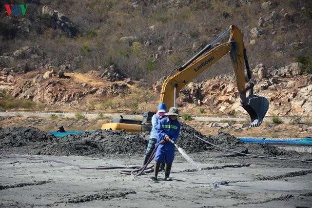 Các công nhân đang phun nước tại bãi tro.