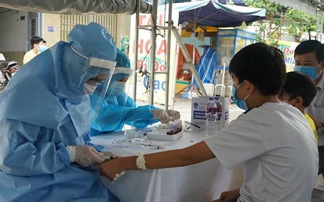Lấy mẫu sinh phẩm của người dân vùng phong tỏa tại Đà Nẵng để xét nghiệm SARS-CoV-2. Ảnh: TTXVN.