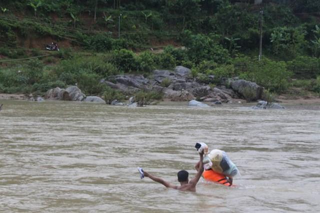 Vượt sông tiếp tế cho đồng bào bị cô lập. Ảnh: Trịnh Minh.
