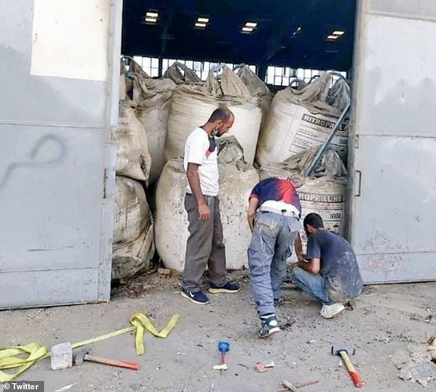 Nhân viên cảng Beirut sửa cửa kho chứa amoni nitrat vài giờ trước vụ nổ. (Ảnh: Twitter).