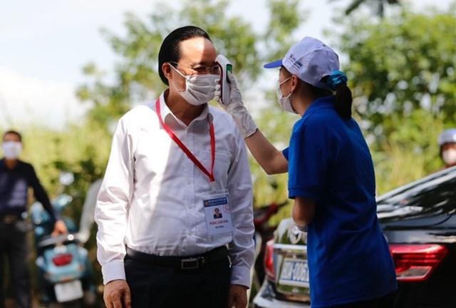 Bộ trưởng được lực lượng Y tế, tình nguyện viên đo nhiệt độ tại điểm thi.