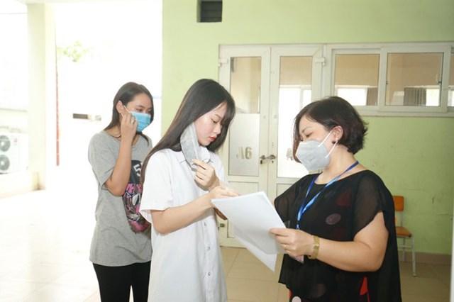 Thí sinh được yêu cầu cởi khẩu trang kiểm tra trước khi vào phòng thi.
