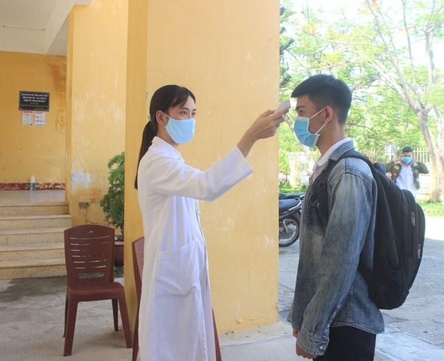 Nhân viên y tế đo thân nhiệt cho các thí sinh.