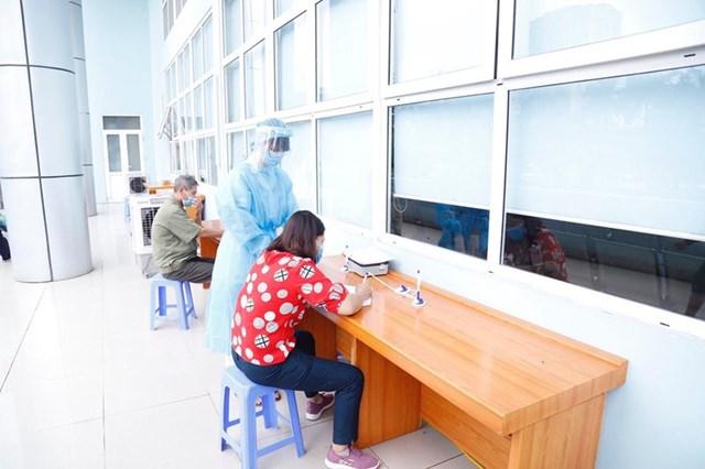 Nhân viên y tế hướng dẫn người dân khai báo thông tin trước khi vào bệnh viện.