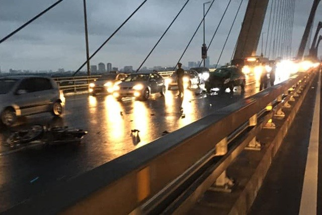 Phóng xe máy ngược chiều trên cầu Nhật Tân, 2 thanh niên tông thẳng vào taxi - Ảnh 1