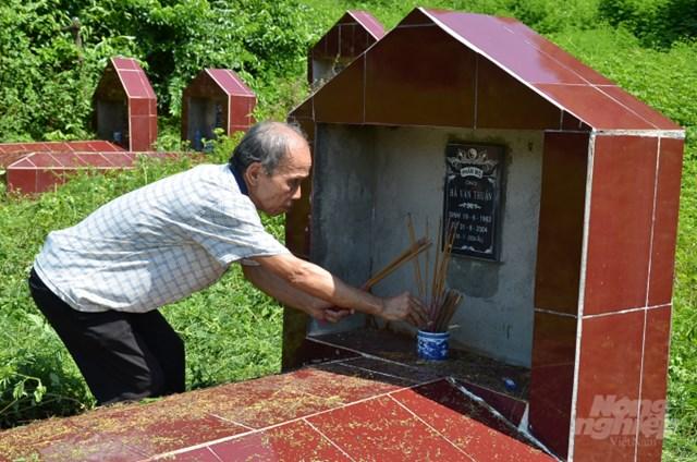 Ông Thiết đang thắp hương cho các ngôi mộ trong dòng họ mình. Ảnh:Dương Đình Tường.