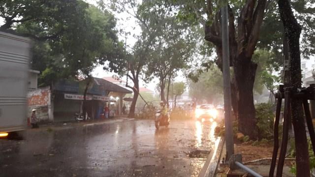 Người đi đường phải tấp vội vào lề đường, hiên nhà để tránh mưa to gió lớn lúc 9h sáng nay 18/9 tại Huế. Ảnh: Dân trí.