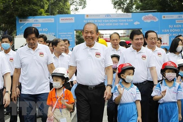 Phó Thủ tướng Thường trực Chính phủ Trương Hòa Bình cùng lãnh đạo các bộ, ngành Trung ương và Thành phố Hồ Chí Minh, các em học sinh tiểu học đi bộ vận động toàn dân 'Đội mũ bảo hiểm cho trẻ em' trên đường Lê Duẩn, quận 1, TP HCM. (Ảnh: Thanh Vũ/TTXVN).