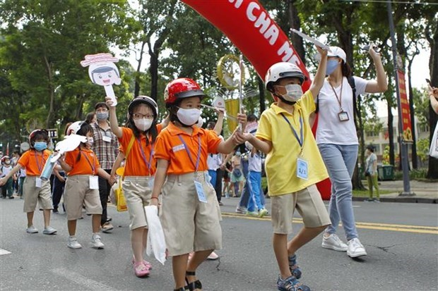 Các em học sinh tiểu học cùng phụ huynh và thầy cô giáo đi bộ vận động toàn dân 'Đội mũ bảo hiểm cho trẻ em' trên đường Lê Duẩn, quận 1, Thành phố Hồ Chí Minh. (Ảnh: Thanh Vũ/TTXVN).
