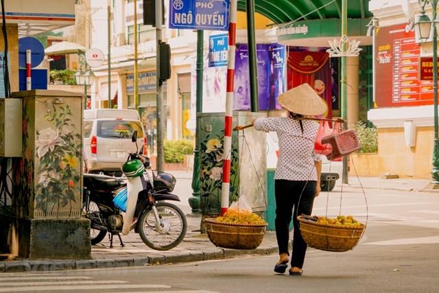 Một Hà Nội hiện đại, nhộn nhịp dường như chậm lại theo bước chân của những gánh hàng rong. (Ảnh: Minh Hiếu/Vietnam+).