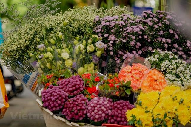 Giữa Hà Nội ồn ào như thế nhưng chỉ một gánh hàng hoa thôi cũng đủ kéo lòng người về miền ký ức xa xôi đầy kỉ niệm. (Ảnh: Minh Hiếu/Vietnam+).