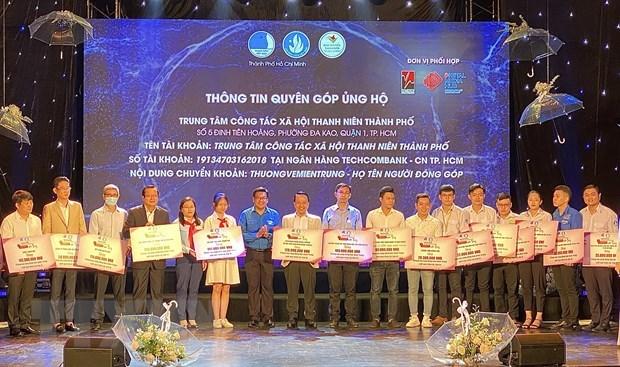 Đại diện các tổ chức, doanh nghiệp, đơn vị trao bảng tượng trưng số tiền ủng hộ miền Trung cho Ban tổ chức. (Ảnh: Hồng Giang/TTXVN).