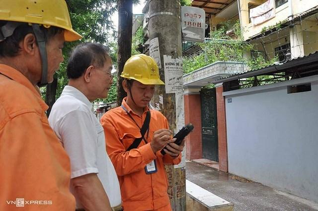 Nhân viên ngành điện đo công tơ điện tử bằng thiết bị đo từ xa sáng 25/4. Ảnh: VnExpress.