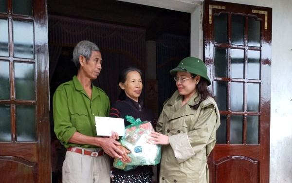 Chủ tịch Ủy ban MTTQ Việt Nam tỉnh Quảng Bình Phạm Thị Hân thăm hỏi một hộ gia đình vừa thoát nạn trong lũ.