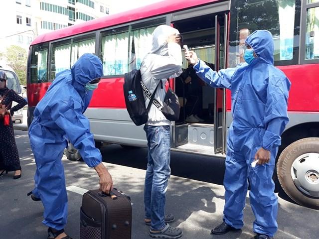 Kiểm tra thân nhiệt các công dân trước lúc lên xe.