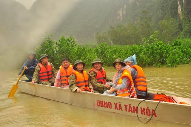 Chủ tịch Ủy ban MTTQ Việt Nam tỉnh Quảng Bình Phạm Thị Hân (người đeo kính) đi thuyền nhôm vào thăm người vùng lũ Tân Hóa.