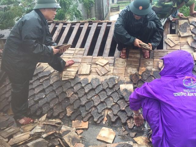 Lực lượng chức năng, chính quyền đoàn thể giúp dân lợp lại mái nhà.
