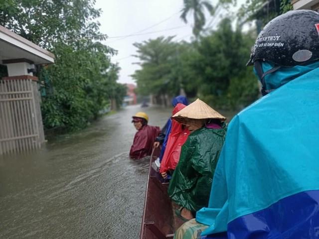 Người dân xã Cẩm Vịnh (huyện Cẩm Xuyên, Hà Tĩnh) lên thuyền đến nơi trú ẩn vì nhà đã chìm trong nước lũ.