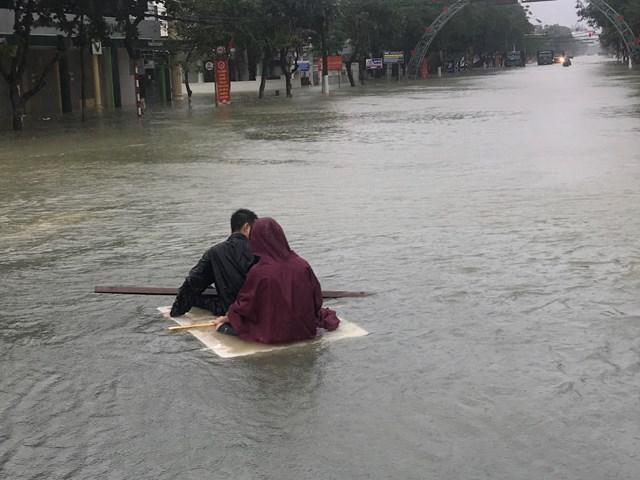 Người dân tận dụng xốp để di chuyển khi đường phố Hà Tĩnh đã biến thành sông.