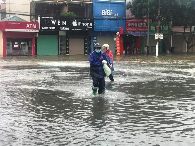 Người đàn ông ở TP Hà Tĩnh lội nước lũ đi mua gạo về tiếp tế cho gia đình.