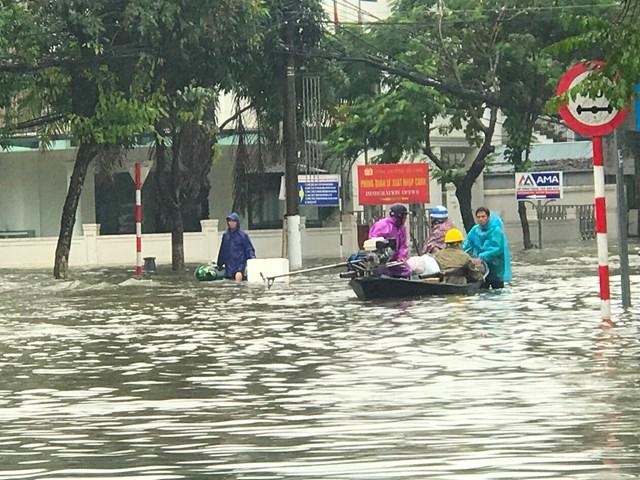 Thuyền cứu hộ đưa người dân ngập lụt ở TP Hà Tĩnh ra khỏi nơi nguy hiểm.