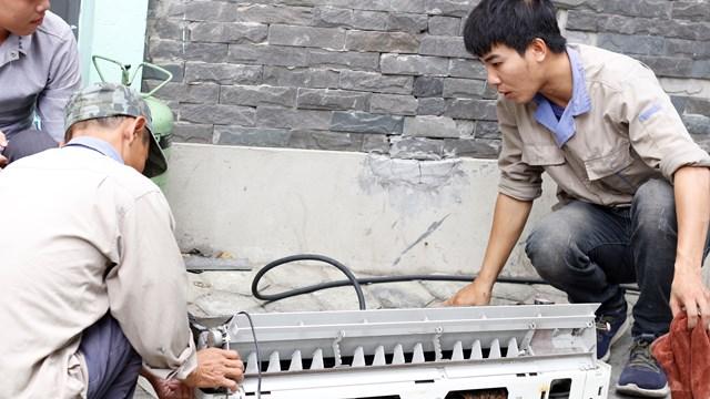 Chú Hùng, 45 tuổi, đồng nghiệp của anh Đức đang vệ sinh vỏ nhựa điều hòa.