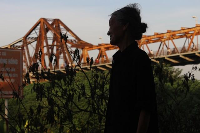 """Bà Ba một cư dân của xóm trọ năm nay đã 70 tuổi đang kể về cuộc sống mấy chục năm lăn lộn ở đất Hà Nội mà đến giờ mới có được một """"căn nhà"""". Với thu nhập một ngày cao nhất là 10.000 đồng nhờ việc nhặt ve chai ở quanh chợ Long Biên, bà nói rằng trời nóng thế này nhưng đành chịu chứ làm sao có tiền mà bật quạt."""