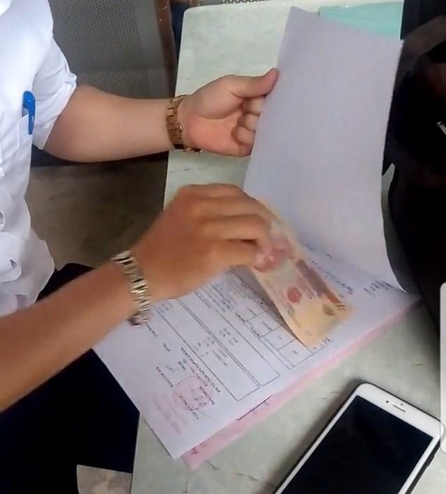 """Hiện tượng """"kẹp"""" tiền diễn ra công khai và dễ dàng ghi nhận tại các điểm đăng ký xe ô tô trên địa bàn Hà Nội."""