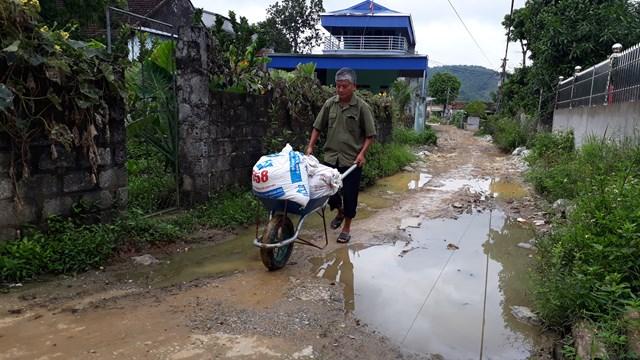 Ông Bùi Văn Cận, ở thôn Hạ Trung Ninh, xã Liêm Sơn phải đẩy thóc ra đường lớn để sát gạo.