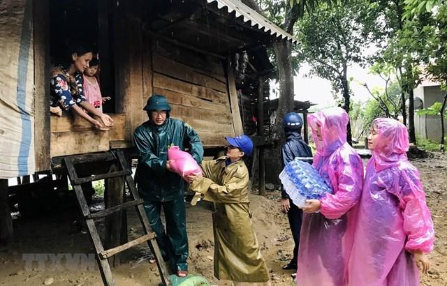 Giúp đỡ nhân dân vùng bị ảnh hưởng nặng nề do lũ lụt ở huyện miền núi Đakrông, Quảng Trị. Ảnh: TTXVN.