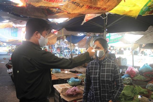 Anh Bình đo thân nhiệt cho tiểu thương chợ Vườn Lài.