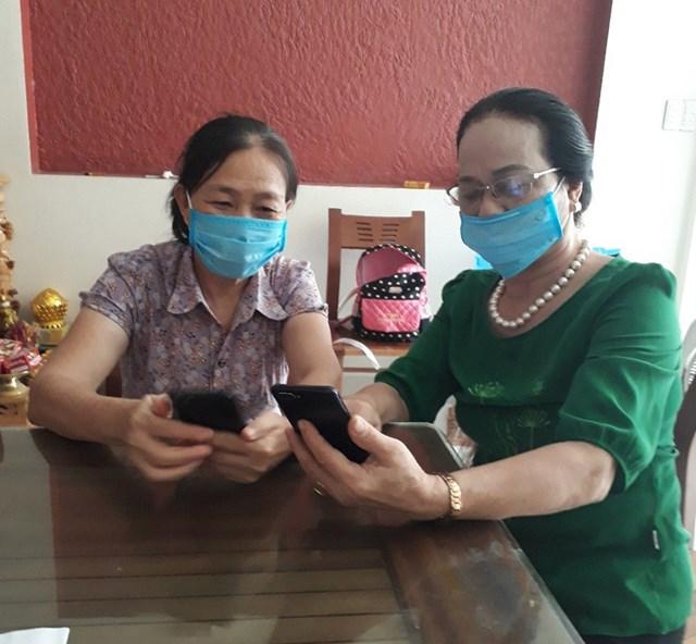 Bà Nguyễn Thị Nhung (phải) hướng dẫn người dân cài đặt ứng dụng Bluezone. Ảnh: Nguyễn Quốc.