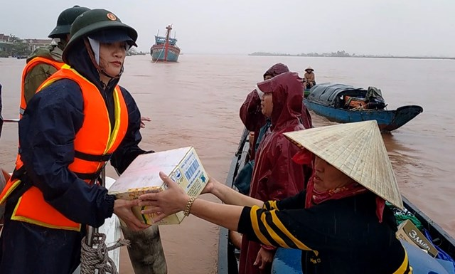 Chị Trần Thị Tuyết Lan, Phó Chủ tịch Ủy ban MTTQ Việt Nam thị xã Ba Đồn trao hỗ trợ người dân ở vùng cồn bãi sông Gianh trong đỉnh lũ.