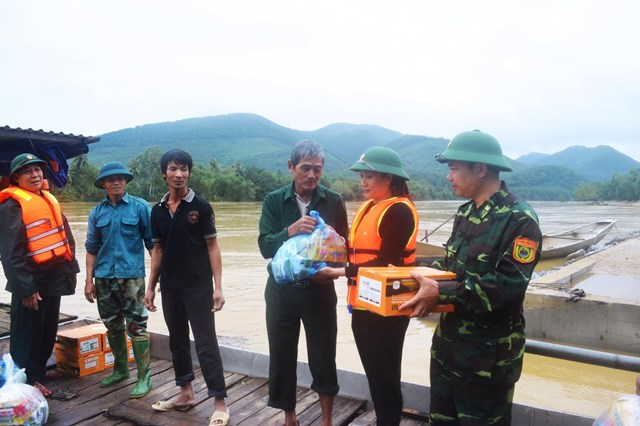 Nữ cán bộ Mặt trận xông pha trên nước lũ để trao tận tay quà cứu trợ cho người dân.