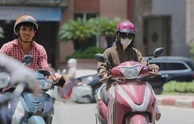 Người dân ra đường với trang phục kín mít để tránh cái nắng gay gắt. (Ảnh: TTXVN).