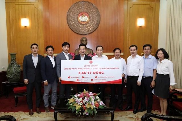 Chủ tịch Trần Thanh Mẫn tiếp nhận bảng tượng trưng số tiền 3,66 tỷ đồng ủng hộ công tác phòng, chống dịch Covid-19 từ đại diện Tập đoàn LOTTE. Ảnh: Quang Vinh.
