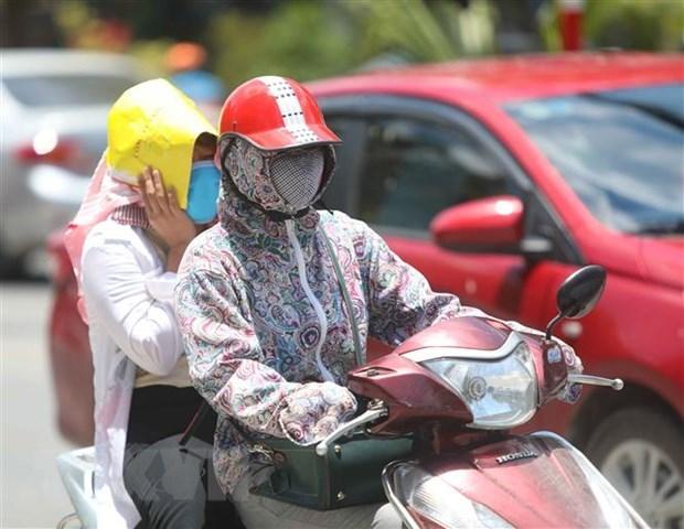 Thời điểm giữa trưa, nếu phải di chuyển trên đường, người dân cần trang bị đồ chống nắng để đảm bảo sức khỏe. Ảnh: TTXVN.
