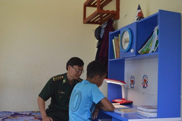Chiến sĩ Đồn Biên phòng Cà Xèng hướng dẫn các em học tập.