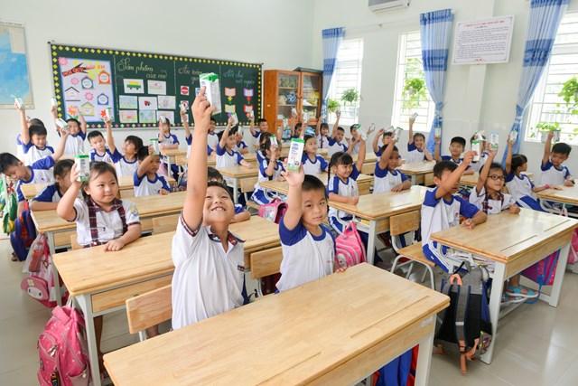 Các em học sinh trường Tiểu học Trang Tấn Khương, xã Long Thới, huyện Nhà Bè vui vẻ đón nhận những hộp sữa an toàn từ chương trình SHĐ.