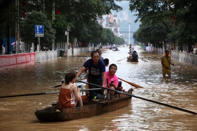 Người dân sử dụng thuyền để di chuyển trong một khu vực bị ngập lụt của thành phố Liễu Châu, Giang Tây, Trung Quốc hôm 11/7 (Ảnh: EPE-EPA).