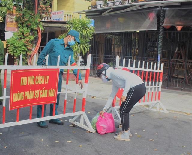 Người dân bên ngoài đưa thực phẩm qua chốt chặn ở khu phố An Hội.